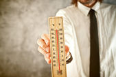 Businessman holding thermometer, measuring high temperatures — Stock Photo
