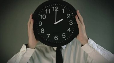 Wasting time. Businessman with clock in front of his head with not enough time to finish the job. — Stock Video
