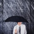 Businessman with black umbrella protecting from rain — Stock Photo