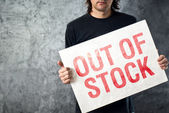 Out of Stock sign in hands of storage employee — Stock Photo