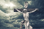 Crucifixion. Christian cross with Jesus Christ statue over storm — Stock Photo