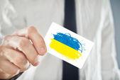 Ukrainian Businessman holding business card with Ukraine Flag — Stock Photo