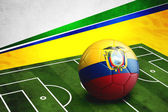 Soccer ball with Ecuador flag on pitch — Stock Photo
