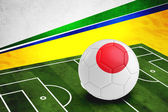 Soccer ball with Japan flag on pitch — Stock Photo