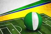 Soccer ball with Nigeria flag on pitch — Stok fotoğraf