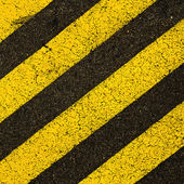 Yellow striped road markings on black asphalt. — Stock Photo