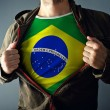 Man stretching jacket to reveal shirt with Brazil flag — Stock Photo