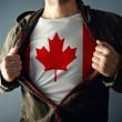Man stretching jacket to reveal shirt with Canada flag — Stock Photo #46169475