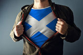 Man stretching jacket to reveal shirt with Scotland flag — Stock Photo