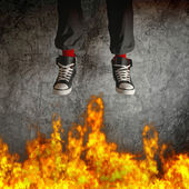 Young man in sneakers is jumping over fire — Stock Photo