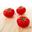 Three Fresh ripe tomatoes on wood table — Stock Photo #46439723