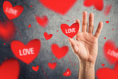 Catching red Valentines hearts with word LOVE printed. — Stock Photo