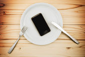 Mobile smart phone served as dinner on white plate — Stock Photo