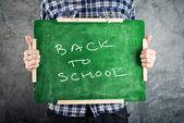 Man holding chalkboard, back to school — Stock Photo