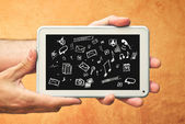 Hands with tablet computer and various doodle icons — Stock fotografie