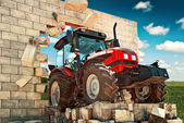 Brand new Tractor breaking through the wall — Stock Photo