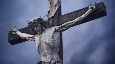 Jesus Christ crucified. The Crucifixion. Christian cross with Jesus Christ statue over stormy clouds time lapse. — Stock Video