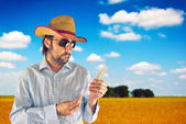 Farmer with cowboy straw hat in wheat field — Stock Photo
