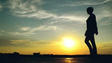 Woman walking on street in sunset. Silhouette of a female person against the beautiful summer sky — Stock Video