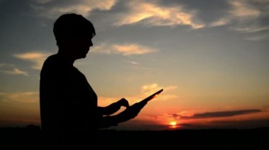 Woman using digital tablet computer for internet browsing. Female silhouette with modern gadget standing in sunset. 1920x1080 full hd footage. — Stock Video