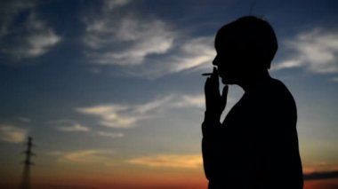 Silhouette of young adult woman smoking a cigarette in sunset. 1920x1080 full hd footage. — Stock Video