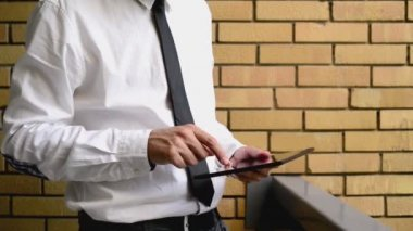Businessman holding digital tablet computer, standing at the office balcony with yellow brick wall. 1920x1080 full hd footage. — Stock Video
