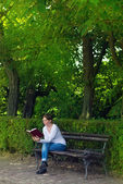 Woman reading book in the park — Zdjęcie stockowe