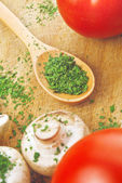 Chopped parsley on wooden spoon — Stock Photo