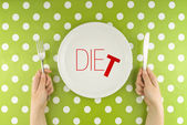 Hands hold flatware above dieting plate — Stok fotoğraf