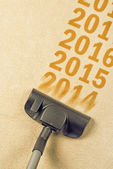Vacuum Cleaner sweeping year number 2014 from carpet — Stock Photo