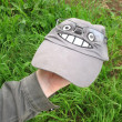 Stock Photo: Cap with image of Japanese cartoon character Totoro while wearing glasses