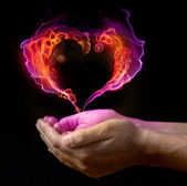 St. Valentin's burning heart on the hands against dark background — Stock Photo