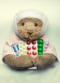 Ill teddy bear in bed — Stock Photo