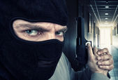 Serious armed criminal with gun — Stock Photo