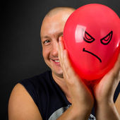 Happy man hiding behind angry balloon — Stock Photo