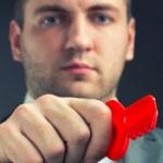 Businessman using red toy key — Stock Photo