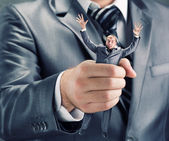 Squeezing small businessman — Stock Photo