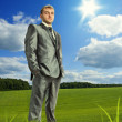Confident businessman on meadow — Stock Photo