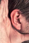Closeup for hand on ear — Stockfoto