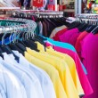 Colorful clothing on hangers — Stock Photo