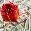 Gift box on heap of money — Stock Photo