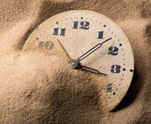Face of clock in sand — Stock Photo
