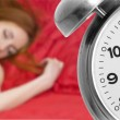 Alarm clock and sleeping young woman — Stock Photo #27451653
