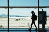 Mulher jovem caminhando no aeroporto — Fotografia Stock