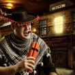 Serious cowboy mexican firing dynamite by cigar — Stock Photo #33039949