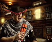 Serious cowboy mexican firing dynamite by cigar — Stock Photo