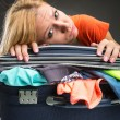Exhausted young woman packing luggage — Stock Photo