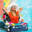 Young woman in suitcase on map — Stockfoto