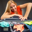 Stock Photo: Womstruggles to shut full suitcase