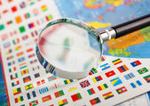 Magnifying glass on the flags — Stock Photo